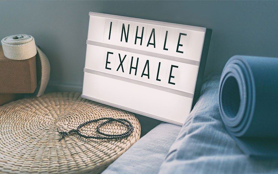 Sign next to a yoga mat reads Inhale, Exhale