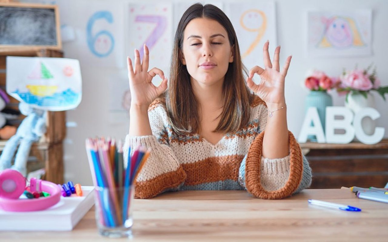 photo of teacher at desk meditating with her eyes closed