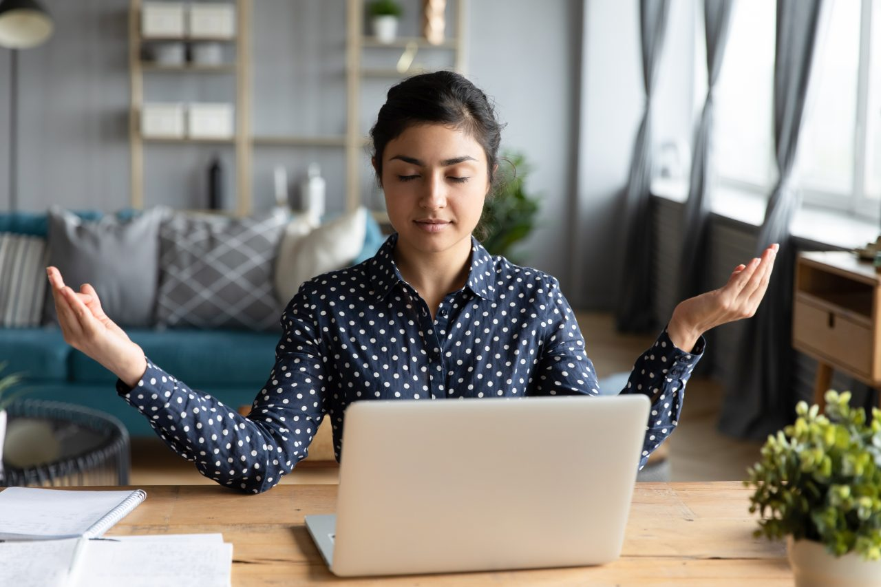 woman meditating with eyes closed in front of laptop