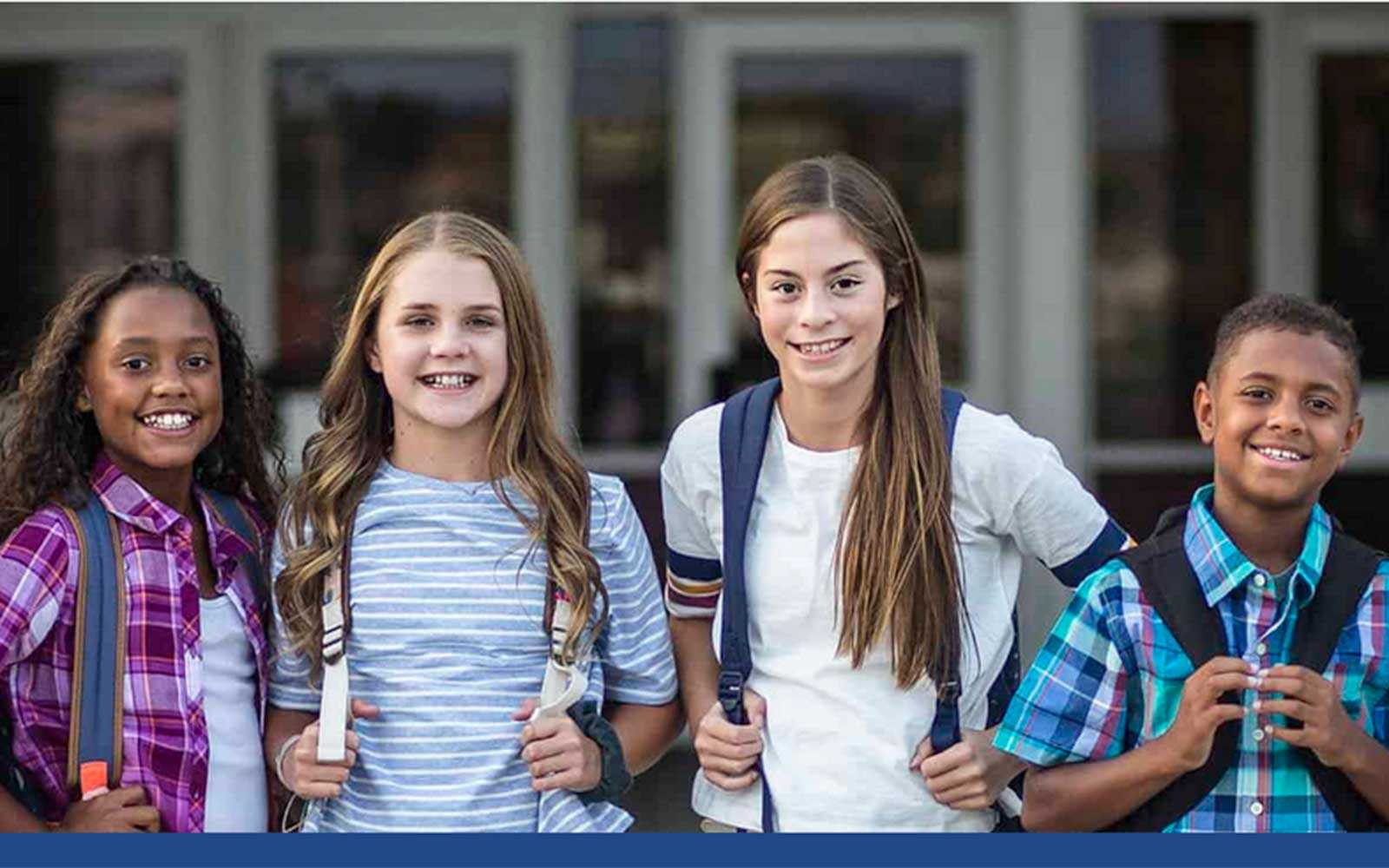 4 middle school students standing in front of school