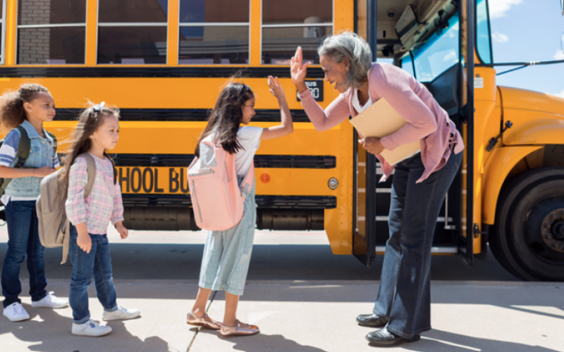 A teacher holding a file folder high fives students as the prepare to load onto a school bus at the end of the school day