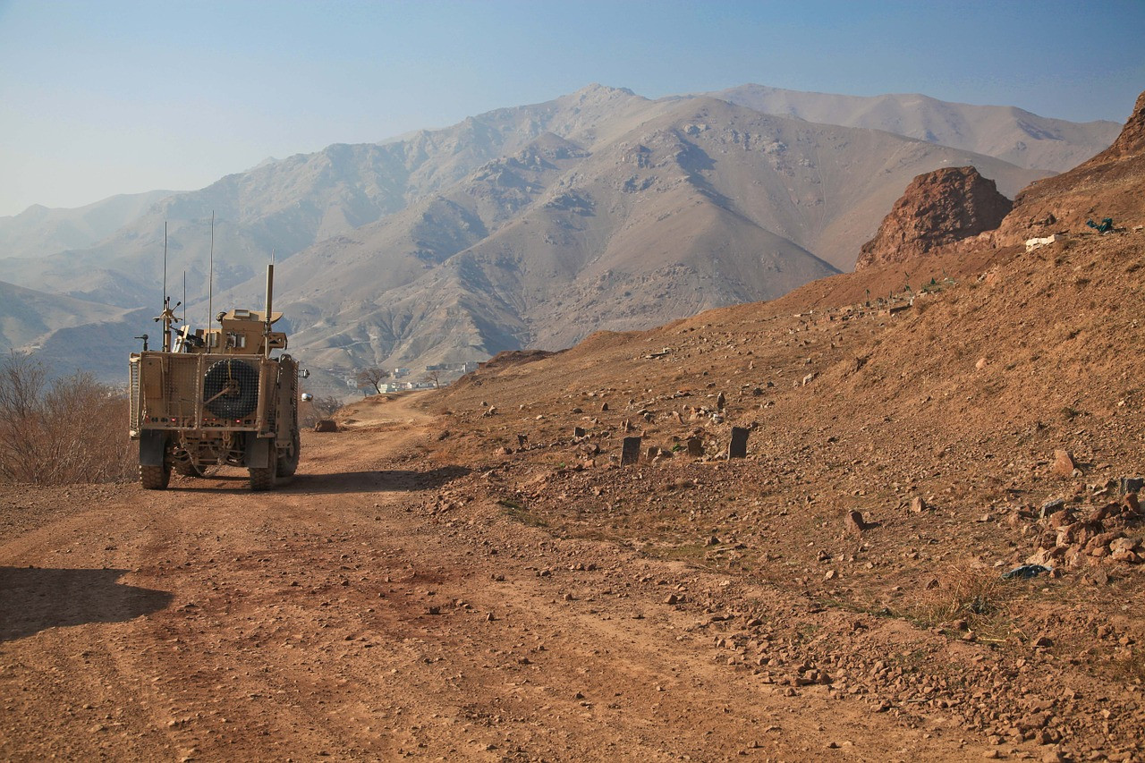 military vehicle driving across the desert