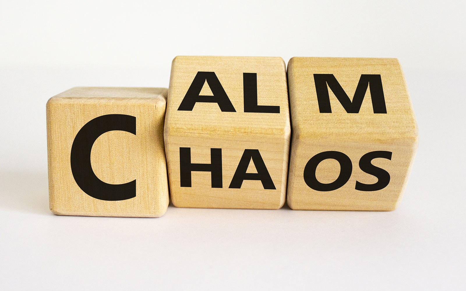 wooden blocks spelling out calm and chaos
