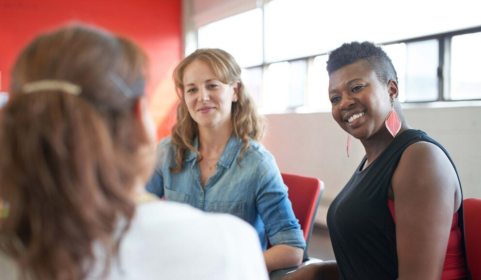Three people having a conversation in the workplace