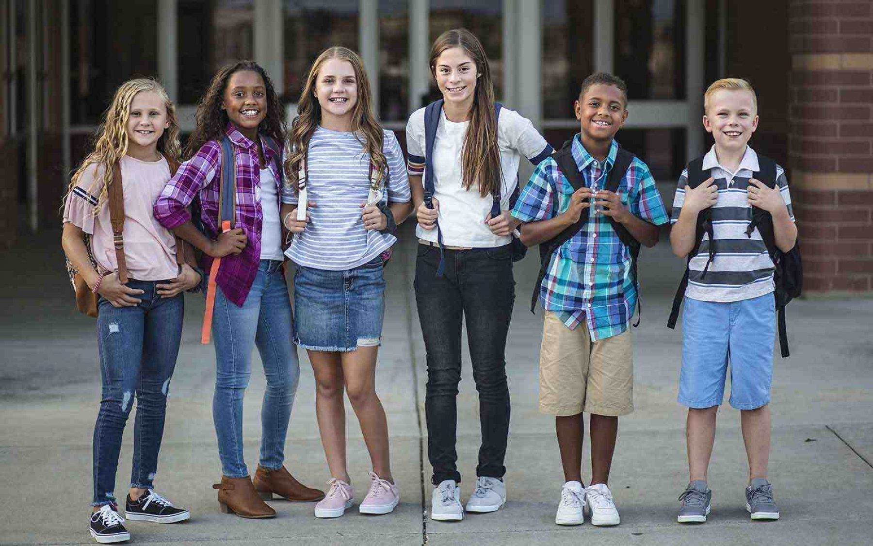 middle school students standing in front of school
