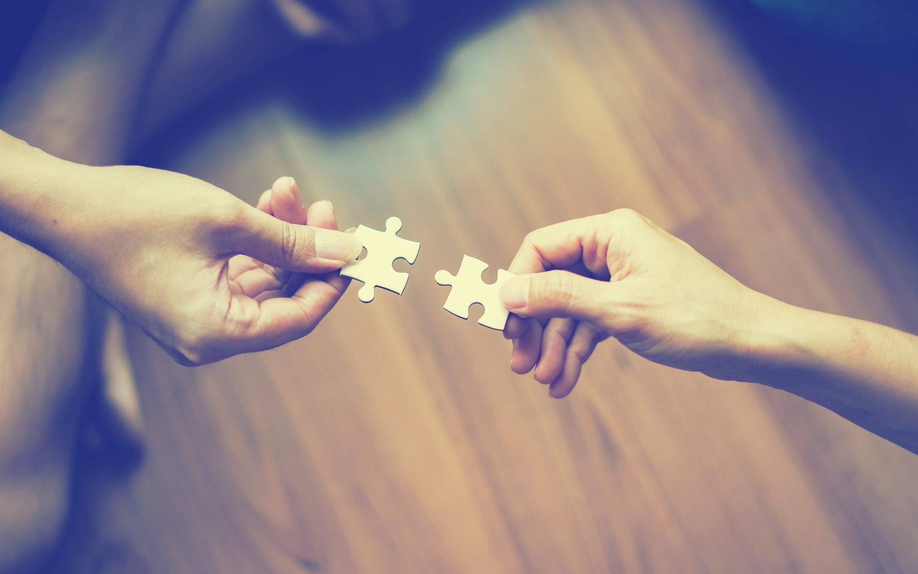 2 hands each with a puzzle piece reaching out to each other