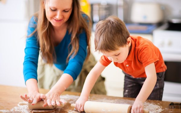 mother rolling dough with young child