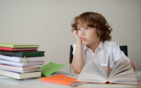 elementary school child looking bored with a stack of books