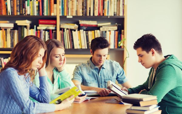 photo of four teens studying around a table