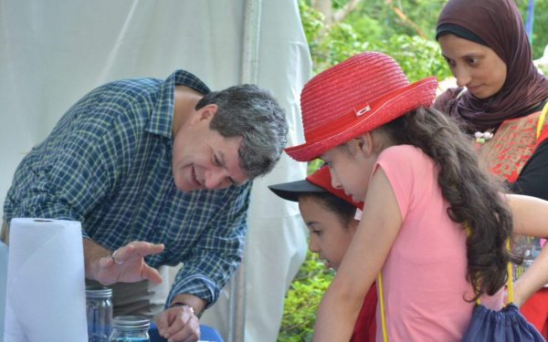 Rob Roeser demonstrates a mindfulness activity using a glass jar to a mother and her two children