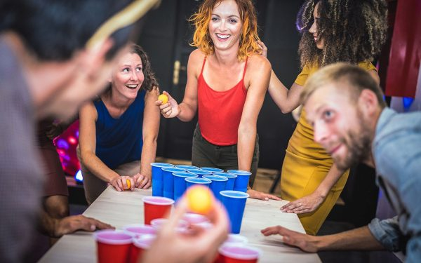 young adults playing beer pong
