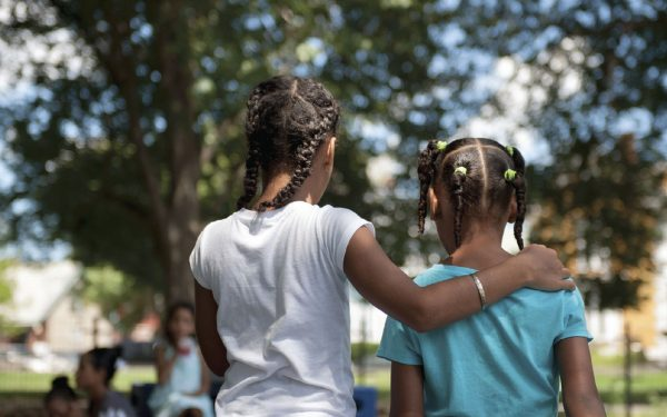 Two young African American girls walking with their arms around one another