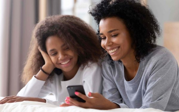 teen girl and mom smiling and looking at mobile phone