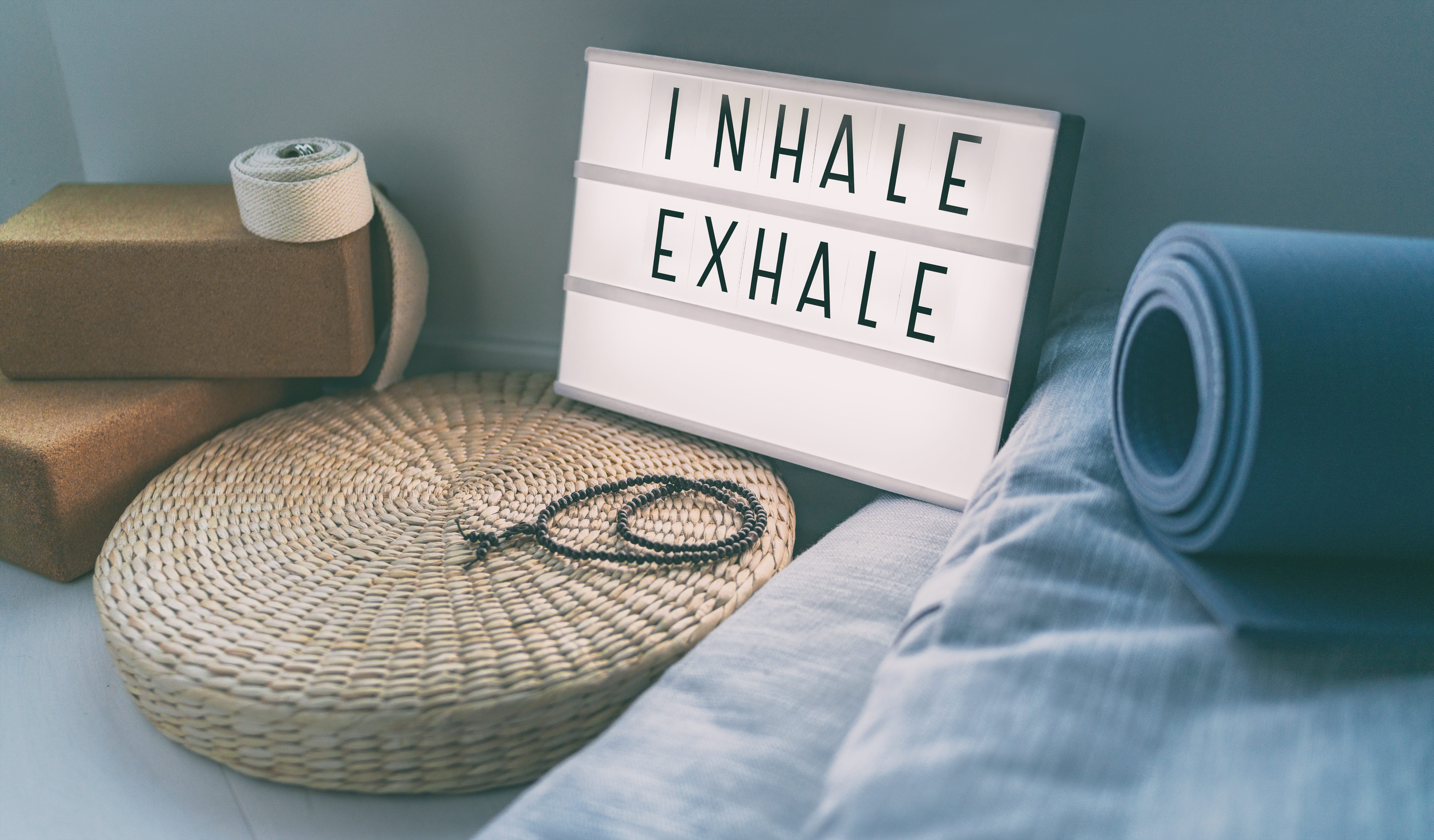 sign that says inhale exhale next to commonly used yoga equipment like a yoga mat